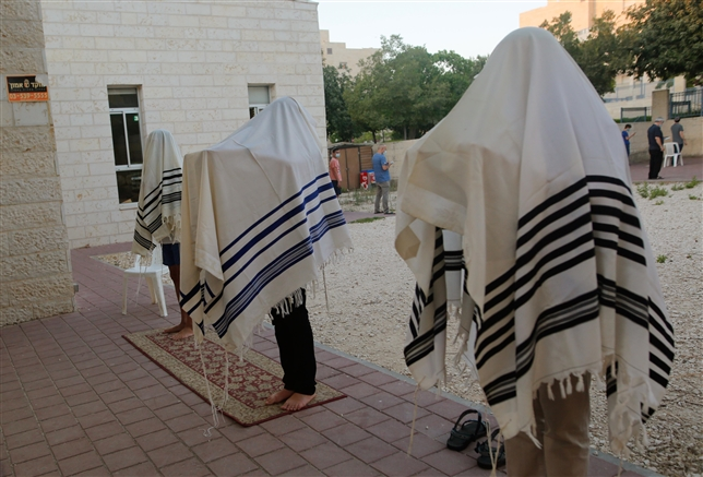 Jewish religious pray outside to insure social distancing spread of the Covid-19 in Modiin
