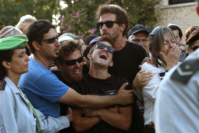 Brothers mourn during a funeral of Israeli soldier July 14
