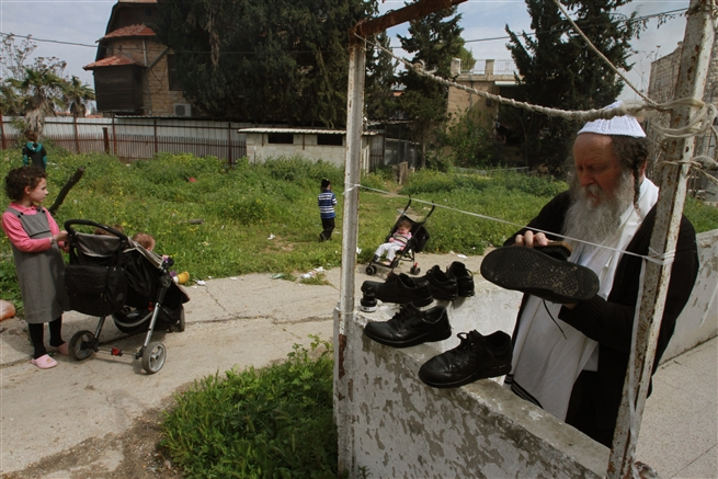 An ultra Orthodox Jewish man brushes his shoes for, Pesahe Jerusalem, April 15
